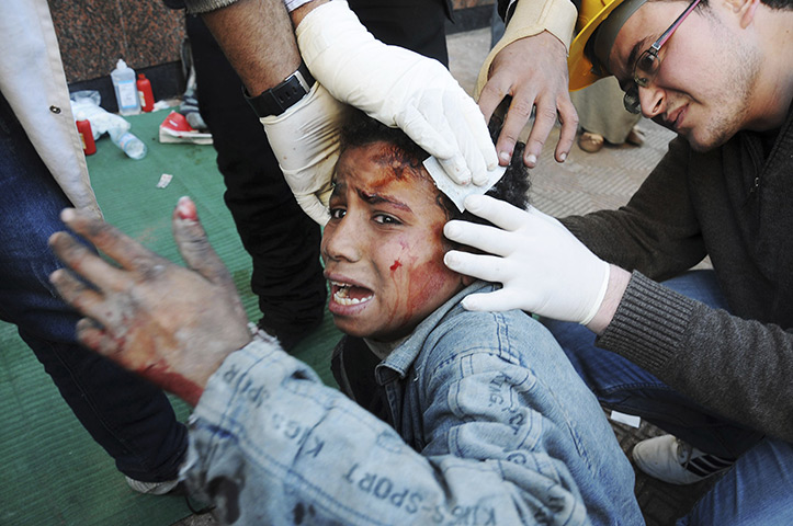 Tahrir Square clashes: Egyptian medics help a young protester near Tahrir Square