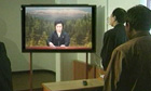 North Korean officials watch a news broadcast announcing death of North Korean leader Kim Jong-il
