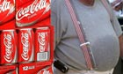 A man passes cartons of Coca-Cola in a store