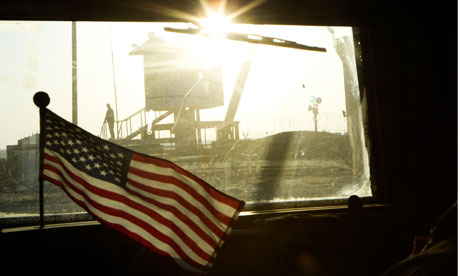 A guard stands on the border of Kuwait seen from the last US military convoy to leave Iraq