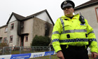 A police officer outside the scene of the fatal house fire in Ayrshire
