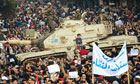 A tank stands amid crowds as protesters gather on Tahrir Square in Cairo.