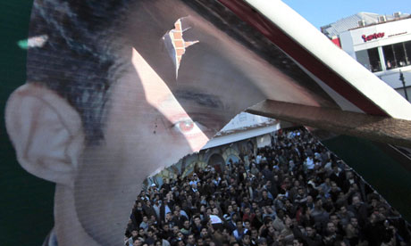 Anti-government protesters demonstrate near a damaged picture of Gamal Mubarak in Alexandria