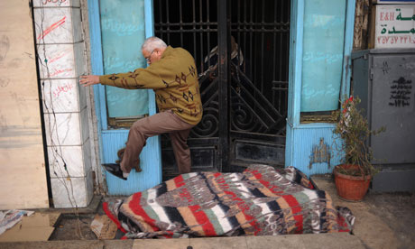 An Egyptian man jumps over an anti-government protester in front of the door of his residence