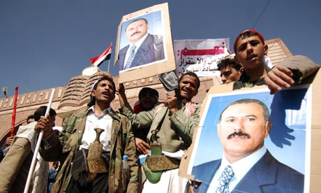 Pro-regime protesters holding posters of their president gather near Sanaa University, Yemen