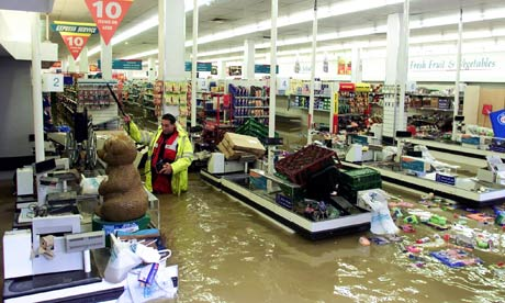 An inspector checks for gas leaks in a flooded supermarket