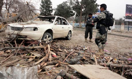 Afghan police inspect a car damaged by the suicide car bomb attack   in Khost