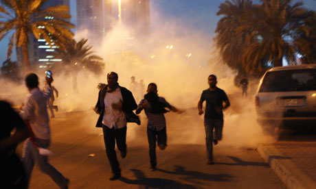 Protesters run from teargas during a clash with Bahraini security forces near the Pearl roundabout