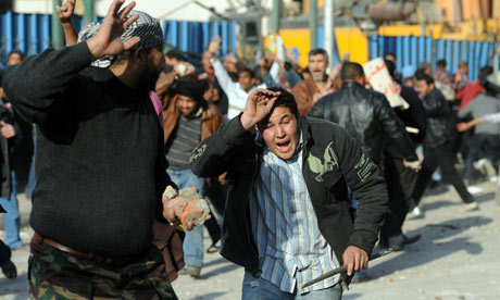 Egyptian protesters run from stones thrown by supporters of Hosni Mubarak during clashes in Cairo