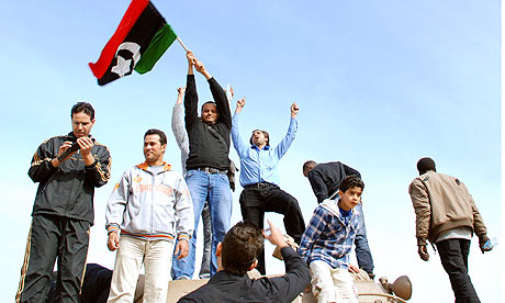 Protesters with a pre-Gaddafi era flag in Benghazi, Libya
