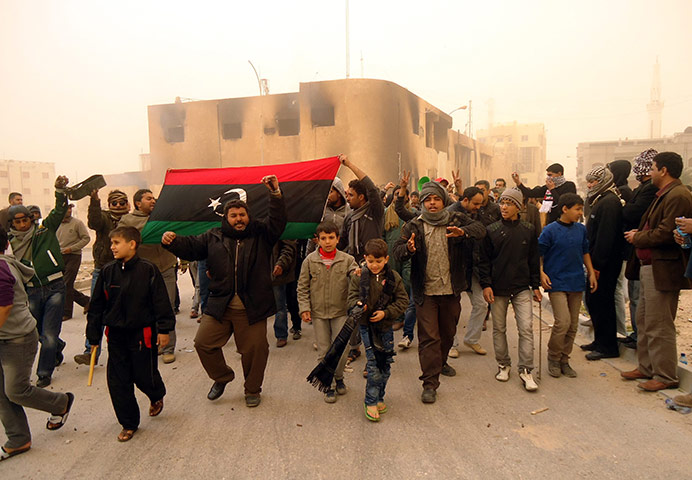 Libya unrest: Libyans hold a flag from the pre-Gaddafi era, during protests in Tobruk