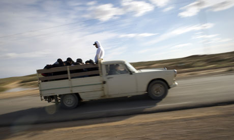 Tunisians travel by pickup truck to the Rad Jdir border post as they escape from Libya
