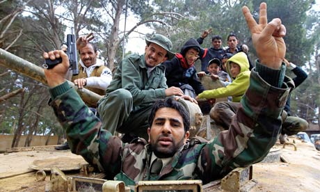 Libyans celebrate atop a captured army vehicle in the eastern city of Shahat