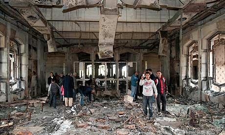 A boy used his mobile phone to capture the wreckage of a room in Gaddafi's palace in Benghazi, now out of the reach of forces loyal to the president