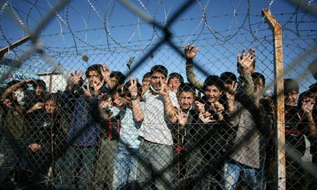Children peer through the fence of an immigrant detention centre on the Greek-Turkish border