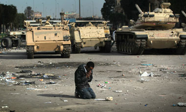 An anti-government demonstrator prays near army vehicles in Cairo, Egypt