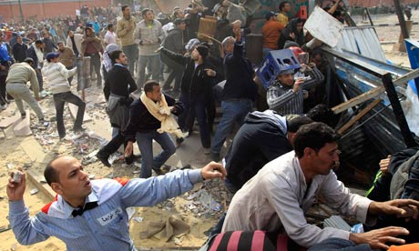 Opposition supporters throw rocks during rioting w pro-Mubarak supporters near Tahrir Square Cairo