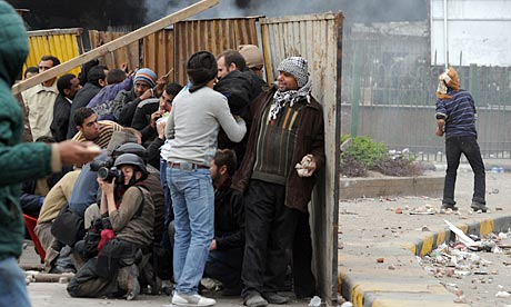 Foreign journalists and Egyptian anti-goverment protesters take cover during clashes