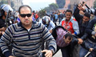 A plainclothes policeman moves to attack a foreign journalist as others beat a protester in Cairo