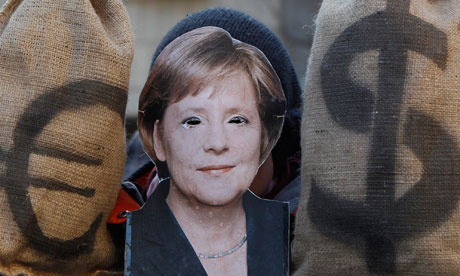 A protester in an Angela Merkel mask