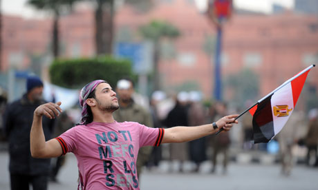 An Egyptian anti-government protester holds the national flag in Cairo's Tahrir Square