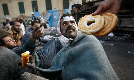 Food is offered to a wounded anti-government protester in Tahrir Square, Egypt
