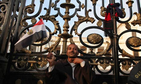 An anti-government protester gestures as he sits outside the Egyptian Parliament in Cairo.