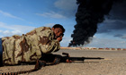 A Libyan rebel fighter lies on the ground as shells fall outside Ras Lanuf