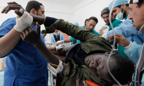 An injured Libyan rebel is treated for a shrapnel injury