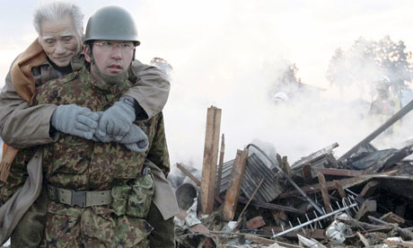 A soldier carries a man to a shelter in Natori after the Japanese earthquake and tsunami