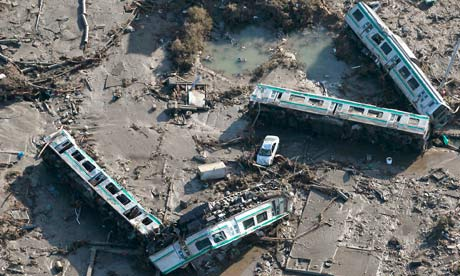 Train carriages lie overturned in Shinchi town after Japan's earthquake-triggered tsunami