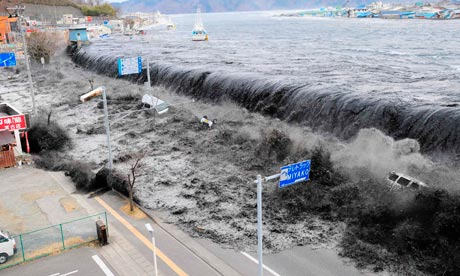Tsunami crashes over a street in Miyako City