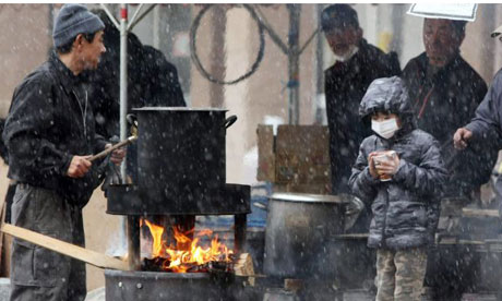 Japan tsunami: A boy waits for boiled water to cook