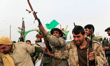 Libyan government soldiers celebrate at the west gate of  town Ajdabiyah
