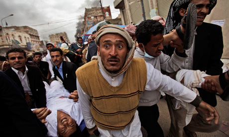 Yemeni protesters carry wounded people from the site of clashes in Sana'a after troops opened fire