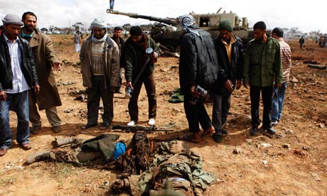People look at the bodies of loyalist soldiers on the outskirts of Benghazi