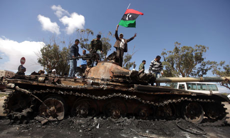 Libyan rebels wave their flag on top of a wrecked tank belonging to Gaddafi's forces in Benghazi