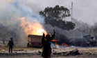 Rebel fighter in front of burning vehicles belonging to Gaddafi's forces