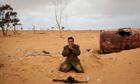 A Libyan rebel prays next to his gun on the outskirts of Ajdabiya