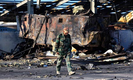 A Libyan soldier walks pass a naval military facility damaged by air strikes in Tripoli