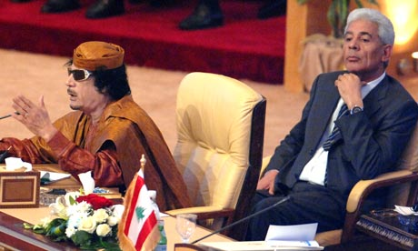 Moussa Koussa sits behind Muammar Gaddafi, the Libyan Ruler, at an Arab League summit in 2009