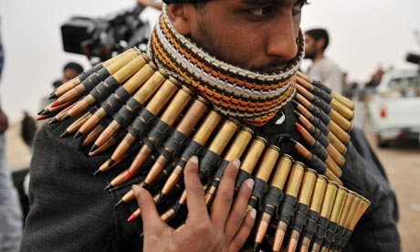 A Libyan rebel fighter wraps himself in ammo