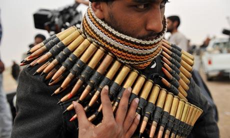 A Libyan rebel fighter wraps himself in ammo