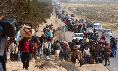Bangladeshi migrant workers fleeing the Libyan violence march toward a UN transit camp in Tunisia