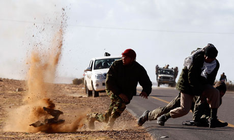 Rebel fighters jump away from shrapnel during heavy shelling near Bin Jawad, Libya