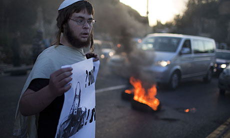 A man holds a sign in support of settlers living in the Havat Gilad outpost