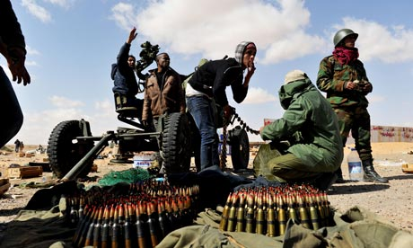 Libyan rebel fighters load ammunition into an anti-aircraft machine-gun at Ras Lanuf