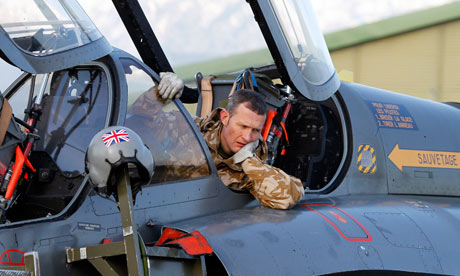 An RAF pilot helps to prepare a French Mirage 2000 fighter jet for a mission to Libya