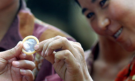 A woman in rural China inspects a condom