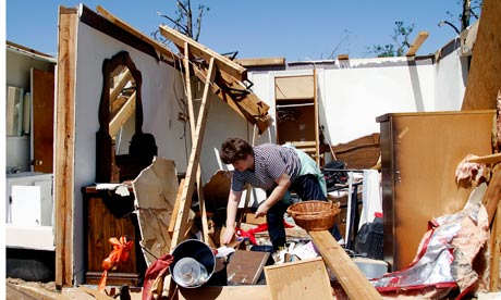 North Carolina resident Deborah Dulow cleans up after the tornadoes
